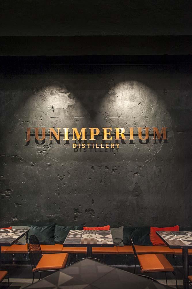 Junimperium-tislaamon logo seinällä